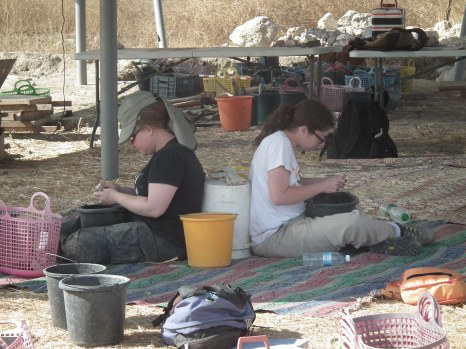 Aviva and Smadar washing pottery while using a pottery bucket in an innovative way